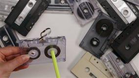 La mujer devuelve a carrete la cinta en el casete audio usando una pluma - visión superior, primer