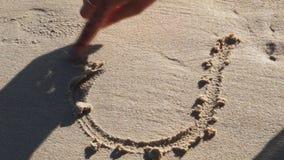 La mujer dibuja el corazón en la arena almacen de metraje de vídeo