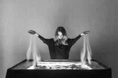 La mujer dibuja en la arena, animación de la arena, arena que se derrama fuera de dos manos Fotografía de archivo libre de regalías