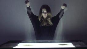 La mujer dibuja en la arena, animación de la arena en un cuarto oscuro almacen de metraje de vídeo