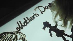 La mujer dibuja en la arena, animación de la arena en un cuarto oscuro el día del ` s de la madre almacen de video