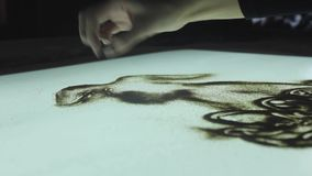 La mujer dibuja en la arena, animación de la arena en un cuarto oscuro para Pascua almacen de video
