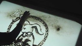 La mujer dibuja en la arena, animación de la arena en un cuarto oscuro para Pascua metrajes