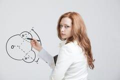 La mujer dibuja la molécula de agua Foto de archivo libre de regalías