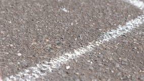 La mujer dibuja una línea en el asfalto con la tiza blanca mano del primer almacen de video