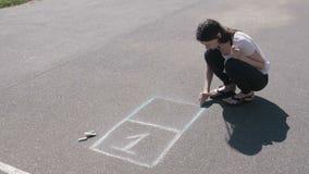La mujer dibuja una rayuela en el asfalto con tizas coloridas almacen de video