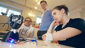 La mujer discapacitada se está moviendo la mano amputada y la mano del robot está haciendo algunos movimientos Los ingenieros son