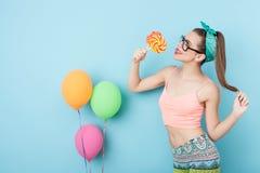 La mujer diseñada joven alegre está comiendo los caramelos imagen de archivo libre de regalías