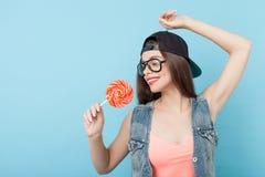 La mujer diseñada joven alegre está presentando con el caramelo Imagen de archivo