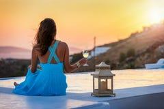 La mujer disfruta de la puesta del sol por la piscina en Mykonos, Grecia fotos de archivo