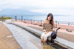 La mujer disfruta de su pie onsen con el gato en al aire libre Foto de archivo libre de regalías