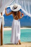 La mujer disfruta de la visión a una playa tropical con una bebida en su mano fotografía de archivo libre de regalías