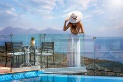 La mujer disfruta del paisaje mediterráneo en Grecia al borde de una piscina foto de archivo