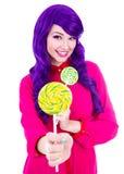 La mujer divertida con el pelo púrpura que daba la piruleta colorida aisló o Fotografía de archivo libre de regalías