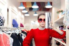 La mujer divertida de la moda en vestido rojo con los vidrios grandes y el hockey shinny empaquetan Fotografía de archivo libre de regalías