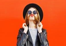 La mujer divertida de la moda que se divierte muestra el pelo del bigote sobre rojo colorido imágenes de archivo libres de regalías