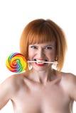 La mujer divertida del pelirrojo exprime la piruleta por los dientes Imagenes de archivo