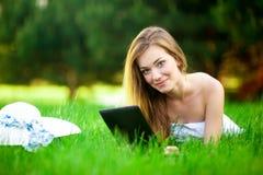 La mujer divertida en el parque guarda su tableta fotografía de archivo