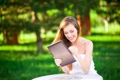 La mujer divertida en el parque guarda su tableta imagen de archivo