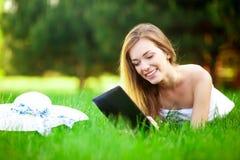 La mujer divertida en el parque guarda su tableta imágenes de archivo libres de regalías