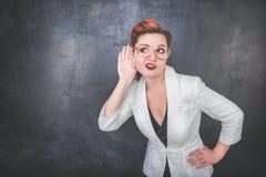 La mujer divertida escucha detras de las puertas en fondo de la pizarra Fotos de archivo