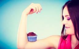 La mujer divertida sostiene la torta de chocolate en el brazo Imágenes de archivo libres de regalías