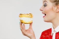 La mujer divertida sostiene la torta del soplo poner crema Fotografía de archivo