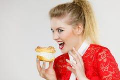 La mujer divertida sostiene la torta del soplo poner crema Foto de archivo