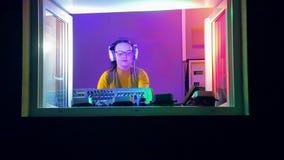 La mujer DJ en auriculares en el cuarto de radio sostiene un disco en la consola de mezcla almacen de metraje de vídeo