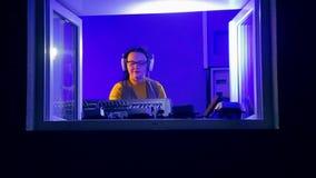La mujer DJ en auriculares en el cuarto de radio sostiene un disco en la consola de mezcla almacen de video