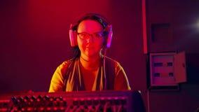 La mujer DJ en auriculares y vidrios en el cuarto de radio sostiene un disco en la consola de mezcla metrajes
