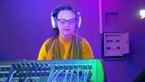 La mujer DJ en auriculares y vidrios en el cuarto de radio sostiene un disco en la consola de mezcla almacen de video