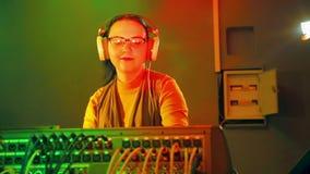 La mujer DJ en auriculares y vidrios en el cuarto de radio sostiene un disco en la consola de mezcla almacen de metraje de vídeo