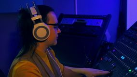 La mujer DJ en auriculares y vidrios mezcla las pistas para el disco en una consola de mezcla almacen de video