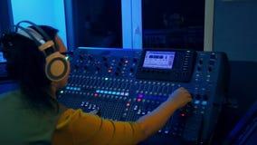 La mujer DJ trabaja en la consola de mezcla en la iluminación del color metrajes