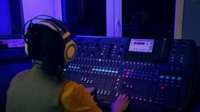 La mujer DJ trabaja en la consola de mezcla en la iluminación del color almacen de video