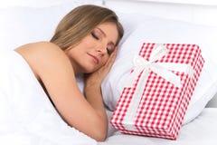 La mujer dormida tiene sorpresa presente esperándola en cama Imagen de archivo