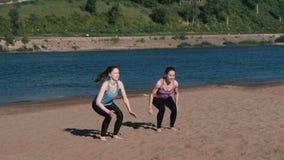 La mujer dos que hace los ejercicios se divierte en los bancos del río en la ciudad Salto de la posición sentada metrajes