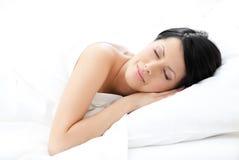 La mujer duerme en cama Fotos de archivo