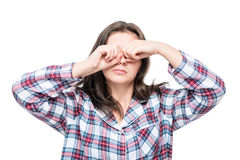 la mujer durmiente en los pijamas que frotan el suyo observa con sus manos Foto de archivo