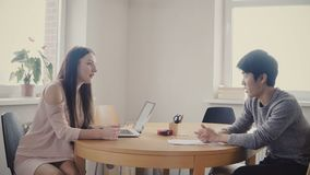 La mujer ejecutiva europea se sienta en la entrevista de trabajo con el trabajador independiente asiático joven Charla multiétnic metrajes