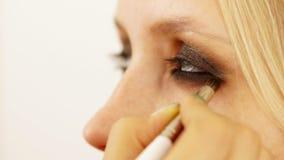 La mujer el artista de maquillaje pone las sombras para los ojos a la muchacha del modelo, está cercana a la cámara Ojos ahumados metrajes