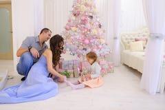 La mujer, el hombre y la niña dan a regalos de Navidad su mitad en s Fotografía de archivo