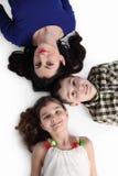 La mujer, el muchacho y la muchacha mienten en piso en gris Fotos de archivo libres de regalías