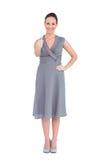La mujer elegante alegre en vestido con clase manosea con los dedos para arriba Imagenes de archivo