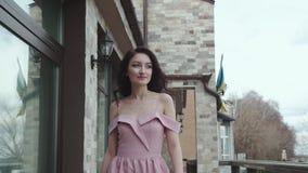 La mujer elegante camina en vestido de noche que sopla, y juegos en el violín metrajes