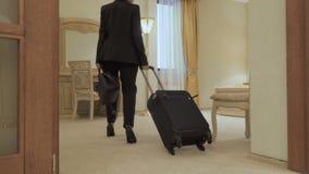 La mujer elegante con la maleta acaba de llegar en una habitación metrajes