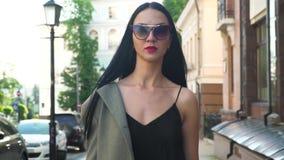 La mujer elegante de la elegancia en gafas de sol y la ropa de moda caminan en la cámara lenta almacen de video