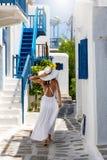 La mujer elegante del viajero camina a través de la ciudad de la isla de Mykonos imagen de archivo libre de regalías
