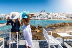 La mujer elegante del viajero dos con los sombreros del sol disfruta de la visión al pueblo de Naousa imagenes de archivo